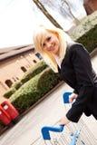 Attraktive Frau, die eine Einkaufenlaufkatze drückt Stockfoto