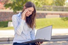 Attraktive Frau, die eine Geschäftsdatei in einem Park liest Stockfoto