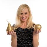 Attraktive Frau, die eine goldene Birne und einen Apfel hält Lizenzfreies Stockfoto