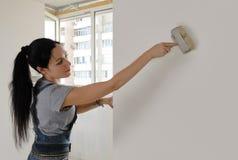 Attraktive Frau, die eine Hausmauer malt Stockfotografie