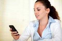 Attraktive Frau, die eine Meldung auf Mobiltelefon liest stockfoto