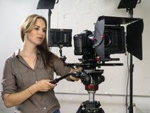 Attraktive Frau, die eine Videokameraanlage laufen lässt lizenzfreies stockfoto
