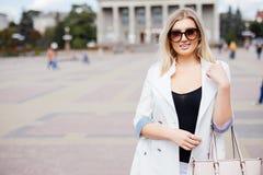 Attraktive Frau, die in einem städtischen Quadrat vor einem großen historischen Gebäude betrachtet die Kamera mit einem warmen fr Stockbilder
