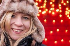 Attraktive Frau, die an einem Weihnachtsmarkt lächelt und steht stockfotos
