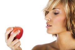 Attraktive Frau, die einen Apfel anhält Stockbild
