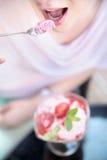Attraktive Frau, die einen Fruchtnachtisch schmeckt Stockfotos