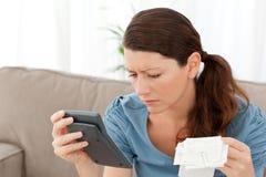 Attraktive Frau, die einen Rechner und Rechnungen anhält Stockbild