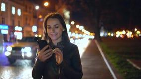 Attraktive Frau, die einen Smartphone beim Gehen durch die Straßen der Glättungsstadt verwendet stock footage