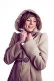 Attraktive Frau, die einen warmen Mantel mit der Haube angehoben trägt lizenzfreies stockfoto
