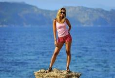Attraktive Frau, die am Felsen frei glaubt vor dem Meer steht Stockfotografie