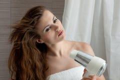 Attraktive Frau, die Fenn im Badezimmer verwendet Stockfoto