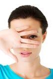 Attraktive Frau, die ihr Gesicht mit der Hand bedeckt. Stockbilder