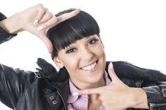 Attraktive Frau, die ihr Gesicht mit ihrem Handlächeln Feld ist Stockfotos