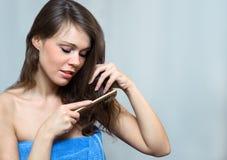 Attraktive Frau, die ihr Haar kämmt Lizenzfreie Stockfotos