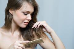 Attraktive Frau, die ihr Haar kämmt Stockbilder