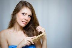 Attraktive Frau, die ihr Haar kämmt Stockfotografie
