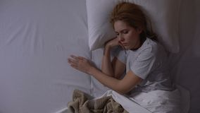 Attraktive Frau, die an ihre letzten Beziehungen sich erinnert, im Bett am Abend, topview zu liegen stock footage