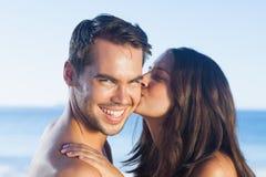 Attraktive Frau, die ihren Freund auf der Backe küsst Stockfotografie