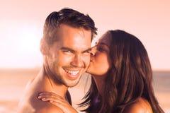 Attraktive Frau, die ihren Freund auf der Backe küsst Stockfoto