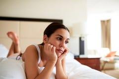 Attraktive Frau, die im Bett schaut traurig liegt lizenzfreies stockbild