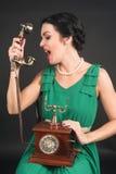 Attraktive Frau, die im Telefon schreit Stockbilder
