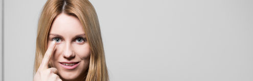 Attraktive Frau, die Kontaktlinsen verwendet Stockbilder