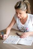 Attraktive Frau, die Kreuzworträtsel tuend sitzt Stockbild