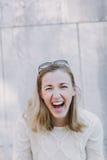Attraktive Frau, die laut über einen Witz lacht Lizenzfreie Stockfotografie