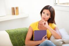 Attraktive Frau, die mit der Hand auf ihrem Kinn sich wundert Lizenzfreies Stockfoto