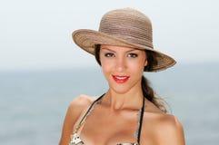 Attraktive Frau, die mit einem Sonnenhut auf einem tropischen Strand lächelt Stockfotografie