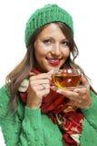 Attraktive Frau, die mit einer Schale heißem Tee aufwärmt Stockbilder