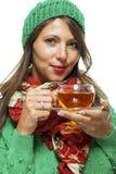 Attraktive Frau, die mit einer Schale heißem Tee aufwärmt Lizenzfreies Stockfoto