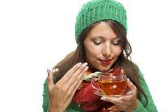Attraktive Frau, die mit einer Schale heißem Tee aufwärmt Lizenzfreie Stockfotos