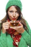 Attraktive Frau, die mit einer Schale heißem Tee aufwärmt Lizenzfreies Stockbild