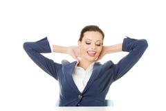Attraktive Frau, die mit ihren Händen hinter ihrem Hals sitzt. Stockfotos