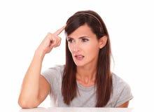 Attraktive Frau, die mit ihrer Hand auf Kopf sich wundert Stockfoto