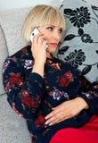 Attraktive Frau, die mit Telefon am Sofa spricht Lizenzfreies Stockfoto