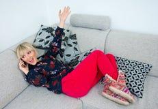 Attraktive Frau, die mit Telefon am Sofa spricht Stockfotografie