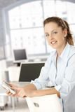 Attraktive Frau, die Mobile beim Bürolächeln verwendet Stockbild