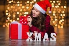 Attraktive Frau, die nahe den Buchstaben buchstabieren Wort Weihnachten und Geschenke liegt Stockfotografie