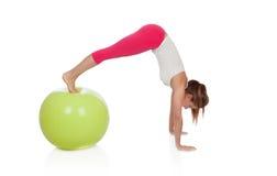 Attraktive Frau, die pilates mit einem großen grünen Ball tut Stockbild
