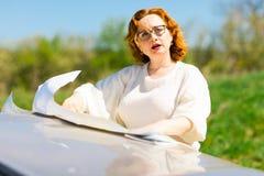 Attraktive Frau, die Position in der Papierkarte auf M?tze ?berpr?ft stockfotografie