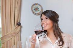 Attraktive Frau, die Rotwein trinkt Stockfoto