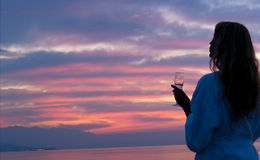 Attraktive Frau, die schönen Sonnenuntergang betrachtet Stockbild