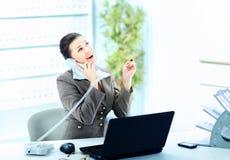 Attraktive Frau, die am Schreibtisch bei der Arbeit auf Überlandleitungtelefonanruf sitzt, Lizenzfreie Stockbilder
