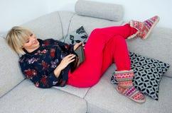 Attraktive Frau, die Tablette im Sofa am hoime verwendet Stockfoto