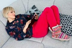 Attraktive Frau, die Tablette im Sofa am hoime verwendet Lizenzfreies Stockfoto