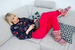 Attraktive Frau, die Tablette im Sofa am hoime verwendet Lizenzfreie Stockfotos