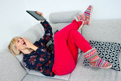 Attraktive Frau, die Tablette im Sofa am hoime verwendet Stockbilder
