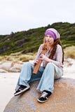 Attraktive Frau, die Ureinwohnerflöte spielt Lizenzfreie Stockfotos